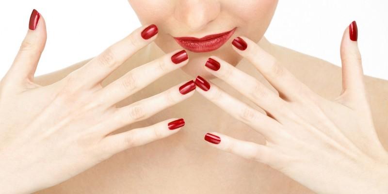 Frau zeigt ihre roten Nägel